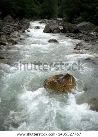 Mountain river. Stone in a mountain river. Rapid flow in a mountain river.