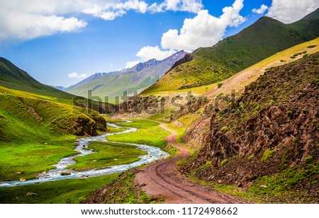 Mountain river valley road landscape. Mountain road at mountain river stream in mountain valley panorama #1172498662