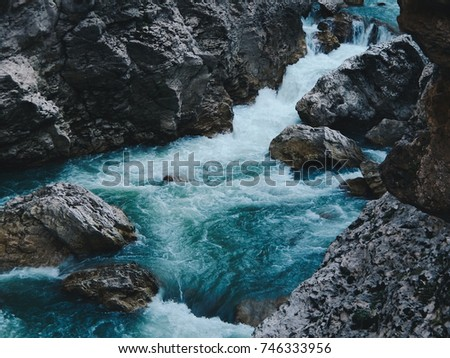 Mountain river with blue water. Wild nature landscape and  grey rocks