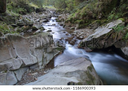 Mountain river with huge, big, and small stones and rocks on riverbed, little waterfalls, long time exposure.