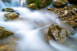Mountain river with small waterfall with clear turquoise water falling down between wet boulders with thick white foam.