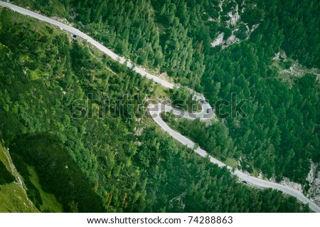 Mountain road aerial view. Asphalt zigzag in green forest.