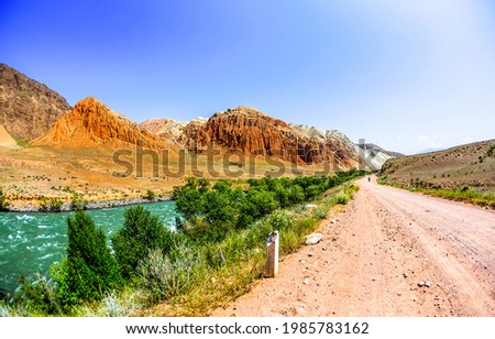 Mountain road along the river. Red sand rock mountain road. Mountain road landscape