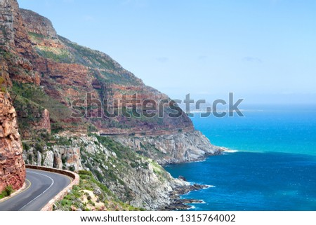 Mountain road along the sea coast, turquoise ocean water seascape, blue sky, azure sea panorama, summer vacation concept, Chapmans Peak Drive road landscape view, Cape Town, South Africa coast travel