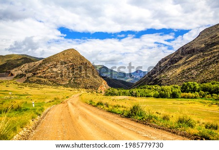 Mountain road among the hills. Road in mountain valley. Mountain valley road landscape