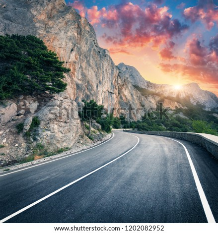 Mountain road and beautiful sky at sunset. Colorful landscape with high rocks, winding asphalt road, trees and blue sky with red and orange clouds in summer. Travel. Scenery with roadway in mountains