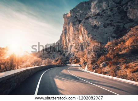 Mountain road and beautiful sky at sunset. Colorful landscape with high rocks, winding asphalt road, trees with orange leaves, blue sky with clouds in autumn. Travel. Scenery with roadway in mountains
