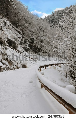 mountain road covered with snow, with guard rail