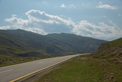 Mountain road in poor condition, has been repaired by patching several times .Winding country road in mountains . Asphalt road in the mountains with soft sky on the background. yellow and white line