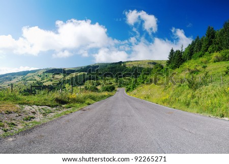 mountain road in spring  under cool sky