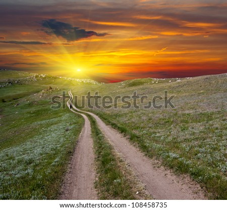 Mountain road on sunset background