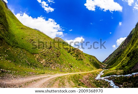 Mountain road through the canyon of green hills. Trail in mountains. Mountain canyon trail. Mountain trail view