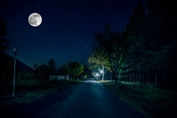 Mountain Road through the forest on a full moon night. Scenic night landscape of dark blue sky with moon. Azerbaijan. Long exposure shot.