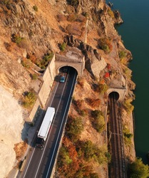 Mountain road tunnels. One tunnel is for cars and the other for trains. Trucks and cars leave the tunnel. Aerial view.