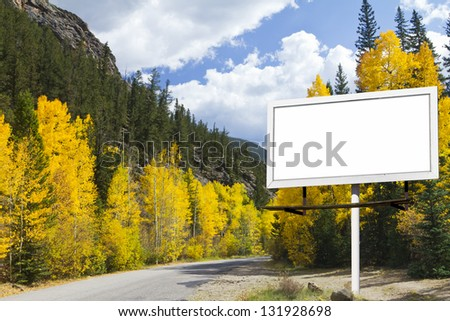 Mountain Road with Blank Billboard Sign and Fall Aspen Trees Forest