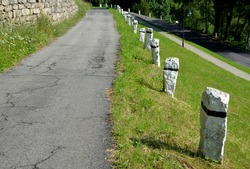 mountain road with traditional white stone bollards with a black stripe. Old stone pillars of granite stone perched on the lawn by the road at regular intervals