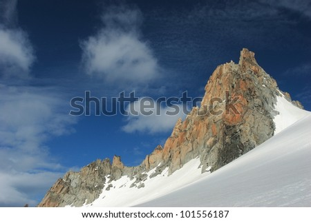 Mountain rock pinnacle in the Alps with dark blue sky, clouds and snow slope.