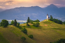 Mountain scenery with church on the mountain ridge. Colorful sunset scenery and cute Saint Primoz church with high mountains in background, Jamnik village, Slovenia, Europe