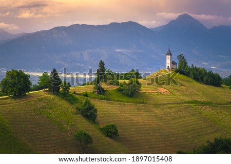 Mountain scenery with church on the mountain ridge. Colorful sunset scenery and cute Saint Primoz church with high mountains in background, Jamnik village, Slovenia, Europe Zdjęcia stock ©
