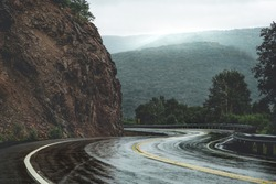 Mountain scenic winding road after the rain. Green forest hills in the background covered by fog. Cape Breton, Cabot Trail, Nova Scotia, Canada