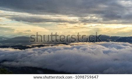 Mountain silhouette above the clouds at sunrise, view from the top view of mountains. #1098759647