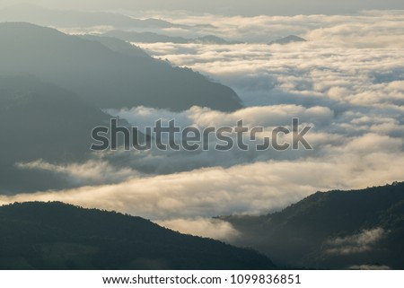 Mountain silhouette above the clouds at sunrise, view from the top view of mountains. #1099836851