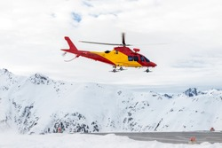 Mountain ski life rescue medic helicopter taking-off from station helipad to search injured skiers and help at accident. Emergency chopper at austrian alpine skiing resort. Alps landsape.