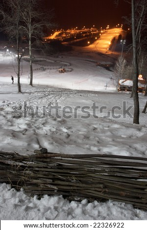 Mountain-skiing slope at night. In the foreground a fence. Small houses-hotels are visible