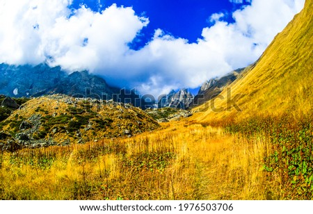 Mountain slope under a cloudy sky. Mountain valley landscape. Mountain clouds view