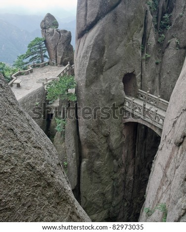 Mountain stone bridge above rocky precipice between the rock. And aerial view at the valley. Huangshan, China, Asia.