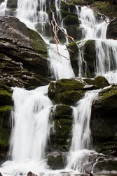 mountain stream in autumn; water falls on the stone stairs