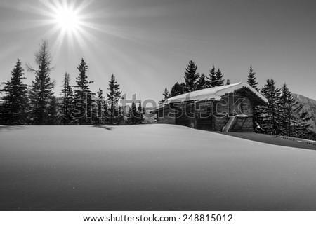 Mountain sun over the ski hut in black and white