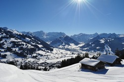 mountain swiss view during winter with wooden chalets