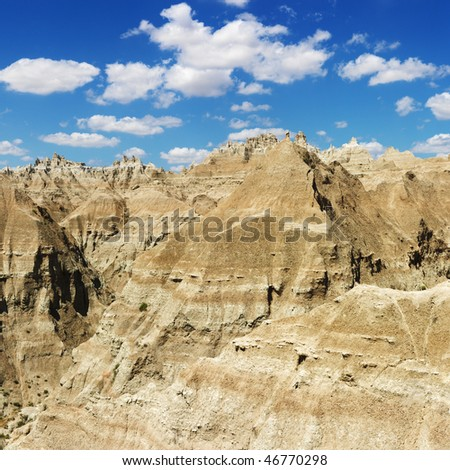 Mountain terrain in Badlands National Park, South Dakota, beneath blue sky and clouds. Square format.