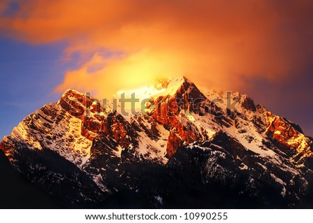Mountain top covered in clouds at sunset