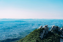 Mountain top in Bukhansan National Park, with city view of Seoul in background.