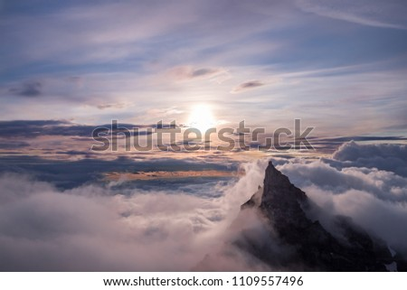 Mountain top peeks above the clouds, illuminated by the sun just after sunrise