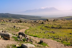 Mountain trail, path going towards snow-covered misty mountain peaks surrounded by ruins of ancient city of Hierapolis, green grass and stones at sunset with sun rays in Pamukkale, Turkey