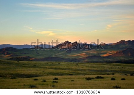 Mountain valley, a pass somewhere in the open spaces of the Tyva Republic, Russia. Evening sunset sky over low mountains and green valley. Soothing mountain warm landscape