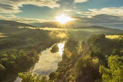 Mountain valley during sunrise. Natural summer scenic landscape with sun rays. Beautiful view of green valley and railway.Sunny day by water. Foggy morning landscape calm atmosphere