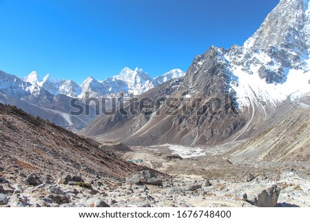 Mountain valley in Himalayas in the morning on the way to Everest base camp in Nepal. Clear blue sky. Dughla village is visible in the middle of photo. heme of beautiful mountain landscapes.
