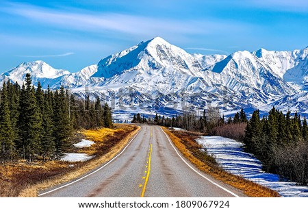 Mountain valley road in winter snow. Mountain road landscape. Road in winter snow mountains. Mountain valley winter road