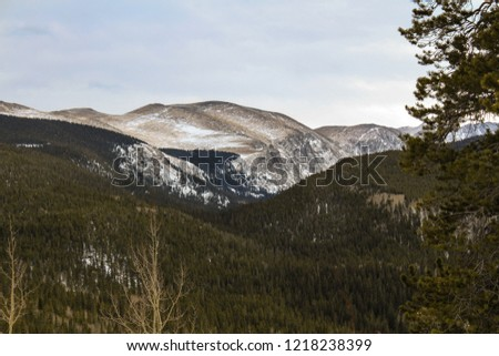 Mountain valley with beautiful forests. Windy winter day in the middle of Rocky Mountains. #1218238399