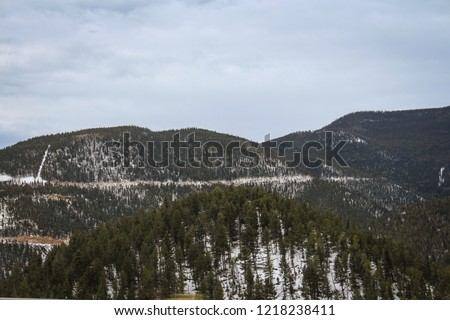 Mountain valley with beautiful forests. Windy winter day in the middle of Rocky Mountains. #1218238411