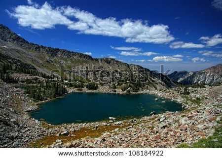 Mountain view from way up above a mountain lake surrounded by huge boulders with a view down toward Salt Lake City Utah under partly cloudy sky's/ Upper Red Pine Lake