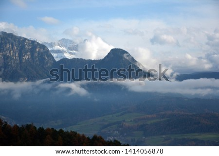 Mountain views along the heritage mountain  rail track from Oberbozen/Soprabolzano to Klobenstein/Collalbo.Snow-capped peaks peeking through the clouds. with trees with autumn leaves in the foreground #1414056878