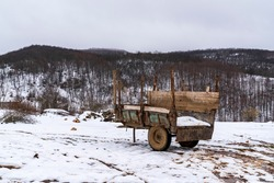 Mountain village and old wagon in snow