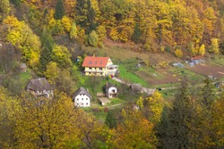 Mountain village slovenian countryside houses and autumn forest with colorful fall trees, Slovenia