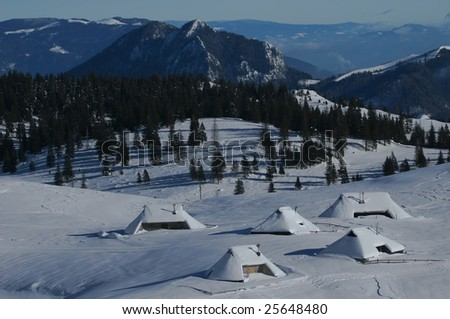 Mountain village with snow covered huts