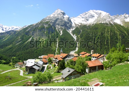 Mountain village with snowy peaks in the background